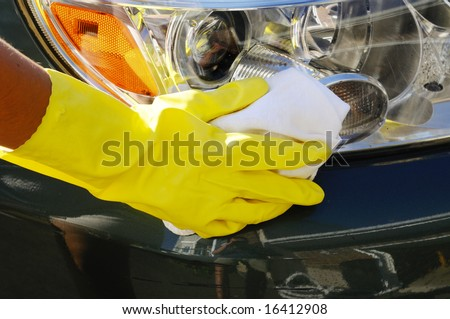 Woman's hand with a rag washing headlights of an SUV car - stock photo