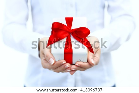 Woman's hand with a small white gift box with bow isolated on white background - stock photo
