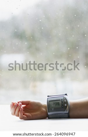 Woman's hand with blood pressure measuring device showing low blood pressure near a window in winter - stock photo