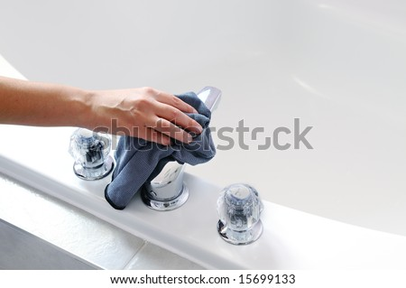 Woman's hand with microfiber cloth cleaning chrome tap - stock photo