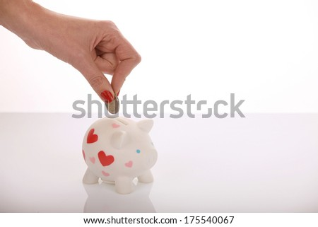 Woman's hand with red nail varnish, on a white background, putting a coin in a piggy bank. - stock photo