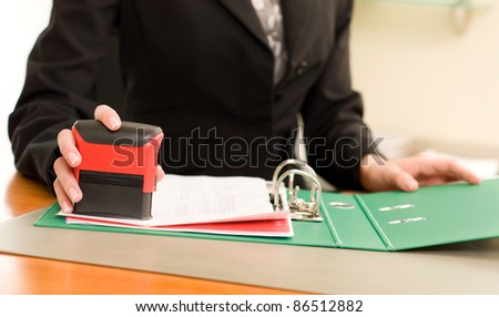 Woman's hand with stamping documents - stock photo