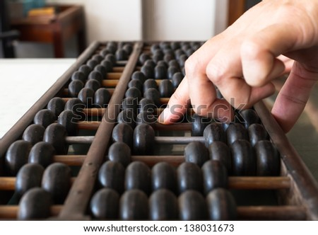 Woman's hands accounting with the old abacus - stock photo