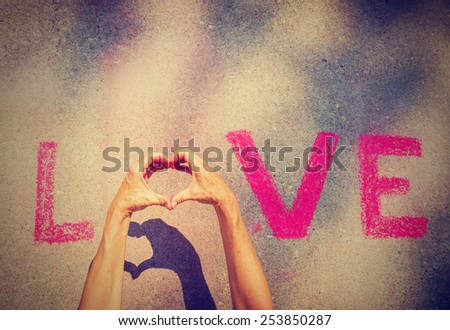 woman's hands creating the O in the word LOVE written in chalk and a shadow underneath the hands with a instagram filter (shallow depth of field) - stock photo