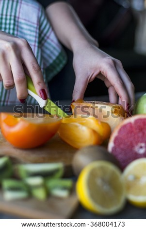 Woman's hands cuts fresh persimmons  - stock photo