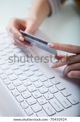 Woman's hands holding a credit card above a keyboard getting ready to enter data - stock photo