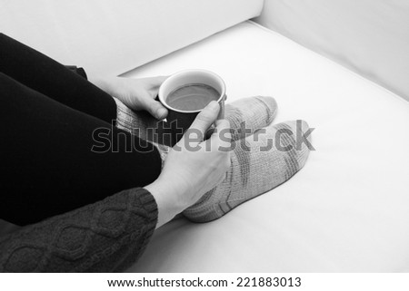 Woman's hands holding a mug of hot coffee or tea, curled up on the sofa, wearing cosy hand-knitted socks - monochrome processing - stock photo