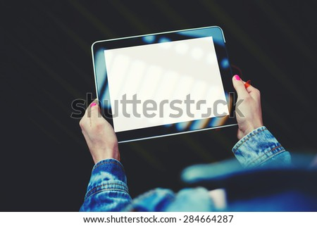 Woman's hands holding digital tablet with blank template copy space screen for your information or content, touch pad with empty display and space for publicity information or advertising text, filter - stock photo