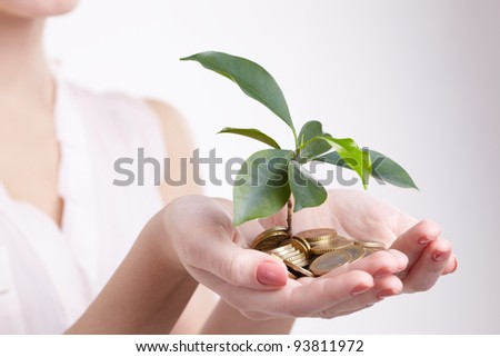 woman's hands holding plant sprouting from a handful of coins - stock photo