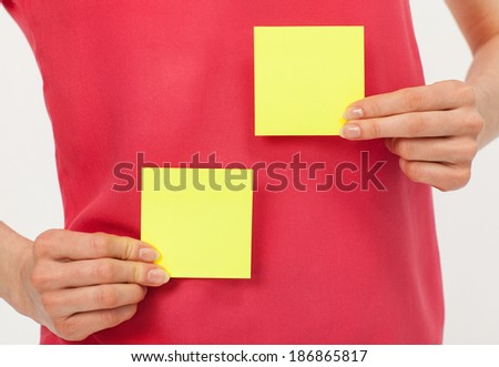 Woman's hands holding two blank yellow stickers over bright red t-shirt - stock photo