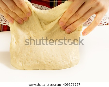 Woman's hands knead dough. - stock photo