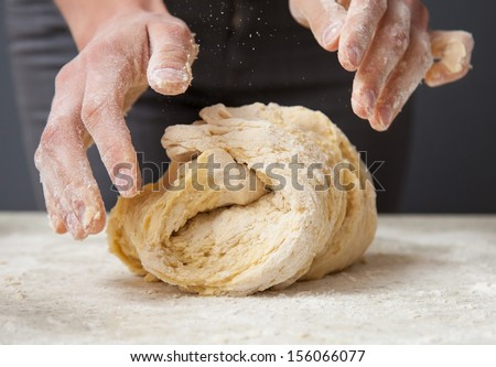 Woman's hands knead dough on a table - stock photo
