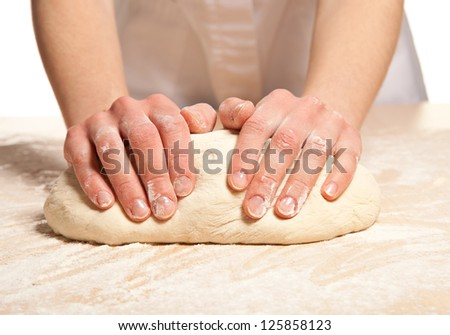 Woman's hands knead dough on wooden table - stock photo