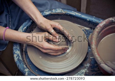 Woman's hands making ceramic cup on potter's wheel  - stock photo