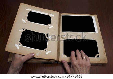 woman's hands on an old vintage photo album - stock photo