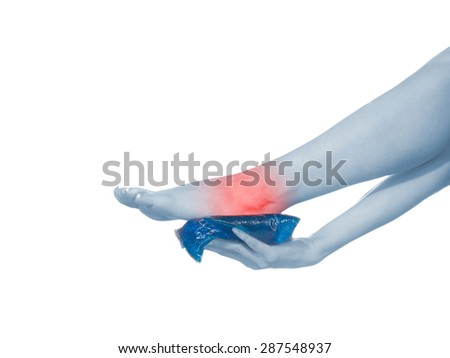 Woman's hands on ankle with Ice Packs for Pain Relief.  Pain medical concept. - stock photo