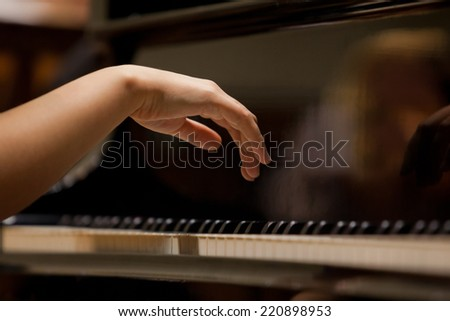 Woman's hands on the keyboard of the piano closeup - stock photo