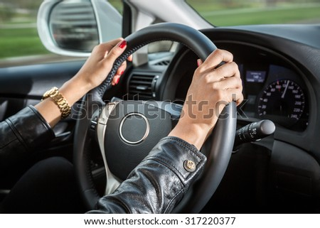 Woman's hands on the steering wheel of the car. - stock photo