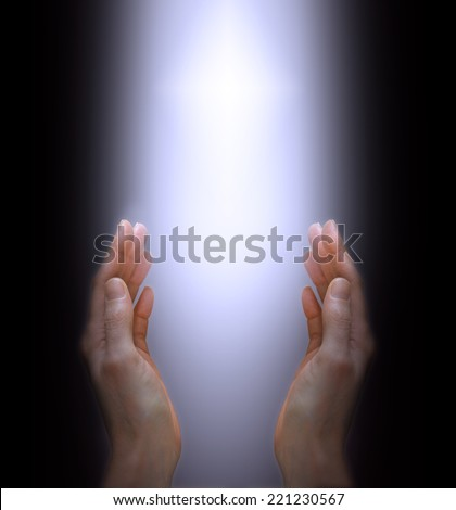 Woman's hands outstretched with shaft of white light and cross between on a black background - stock photo