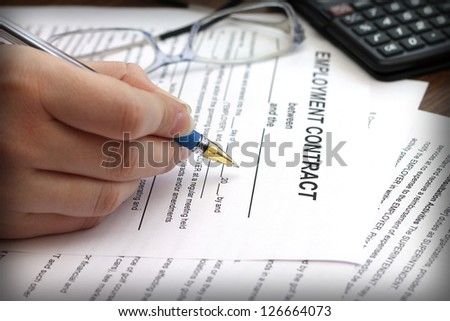 woman's hands signing an employment contract, close-up - stock photo