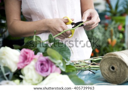 Woman's hands tying together a bouquet of pink and white roses - stock photo