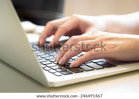 Woman's hands typing on laptop keyboard : Selective Focus - stock photo