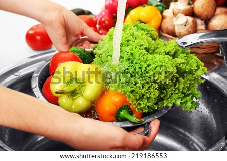 Woman's hands washing vegetables in sink in kitchen - stock photo