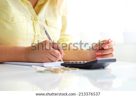 Woman's hands with a pen and a calculator in office - stock photo