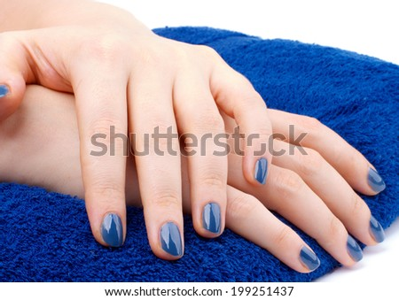 Woman's Hands with Blue Manicure on Dark Blue Towel isolated on white background - stock photo