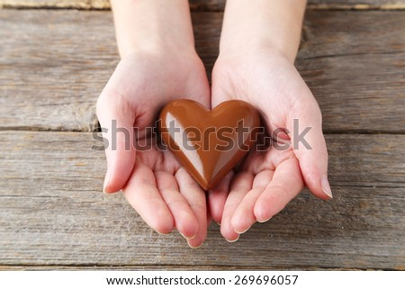 Woman's hands with chocolate heart - stock photo