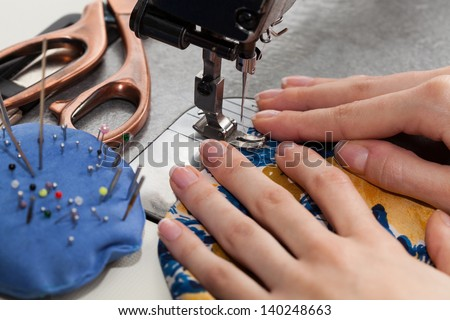 Woman's hands with dress at sewing machine - stock photo