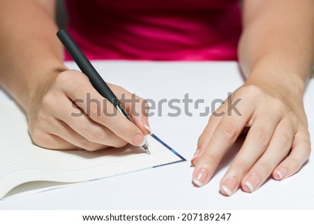Woman's Hands With French Manicure Holding A Pen Writing A Text - stock photo