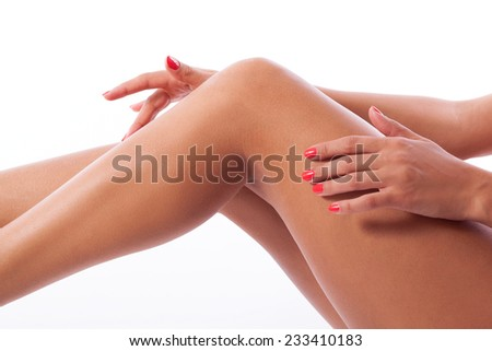 woman's hands with red manicure palming beautiful slim sexy naked legs  - stock photo