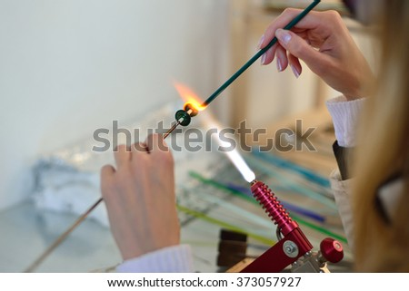 woman's hands with tools for glass melting, lampwork - stock photo
