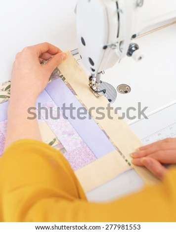 Woman's hands working on sewing machine. - stock photo