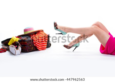 Woman's legs and filled suitcase. Filled suitcase on white background. Entire wardrobe in single bag. Too much haste. - stock photo
