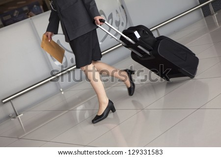 Woman's legs and travel suitcase - stock photo