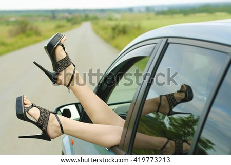 Woman's legs in high heel shoes out in a car window outdoor. reflection in glass. no face. unrecognizable person. slim caucasian white girl - stock photo