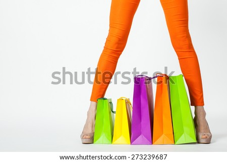 Woman's legs in orange pants and multicolored shopping bags, copyspace - stock photo