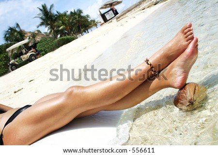 Woman's legs resting on a coconut in tropical water - stock photo