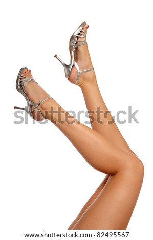 Woman's legs wearing high heels isolated on a white background - stock photo