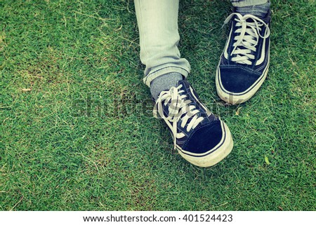 Woman's legs wearing jeans with sneaker sitting on the grass. - stock photo