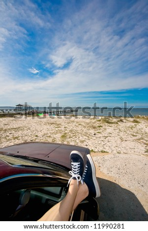 Woman's legs with canvas sneakers dangling out a car window parked at the beach - stock photo