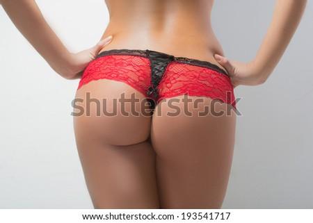 Woman's sexy buttocks in a bikin.  light background - stock photo