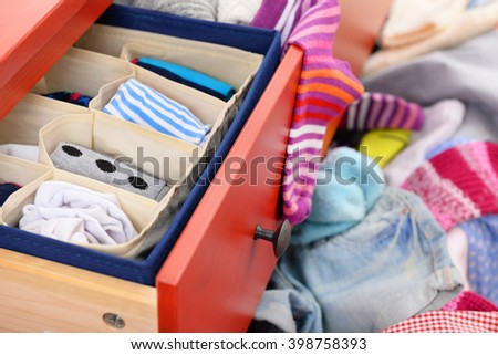 Woman's sock and pile of clothes in open drawer, close up - stock photo
