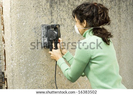 Woman sands wall with a power sander. She is wearing a dust mask. Horizontally framed photo. - stock photo