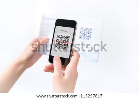 Woman scanning QR code in the magazine on mobile smart phone. - stock photo