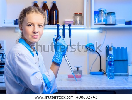 Woman scientist biochemist at the workplace makes the analysis in the modern laboratory. She is holding a dropper and a test tube - stock photo