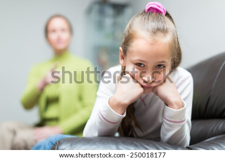 Woman scolding sad little daughter at home interior   - stock photo