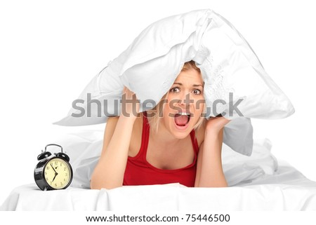 Woman screaming and covering her ears with pillow because of noise - stock photo